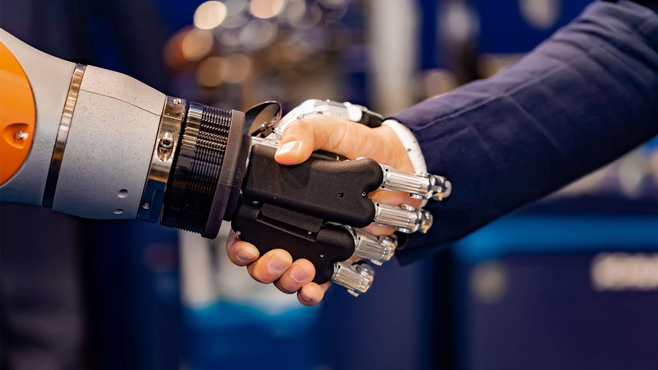 Mano umana e mano robotica si stringono in un saluto