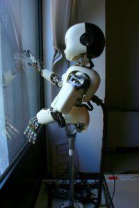Robot dietro una finestra, che guarda fuori